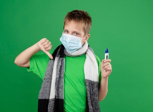Petit garçon malade en t-shirt vert et écharpe chaude autour de son cou portant un masque de protection du visage tenant un thrémomètre se sentant nwell montrant les pouces vers le bas debout sur fond vert