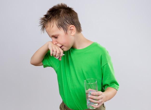 Petit garçon malade en t-shirt vert se sentir mal tenant un verre d'eau et de pilules essuyant le nez avec une serviette en papier debout sur un mur blanc