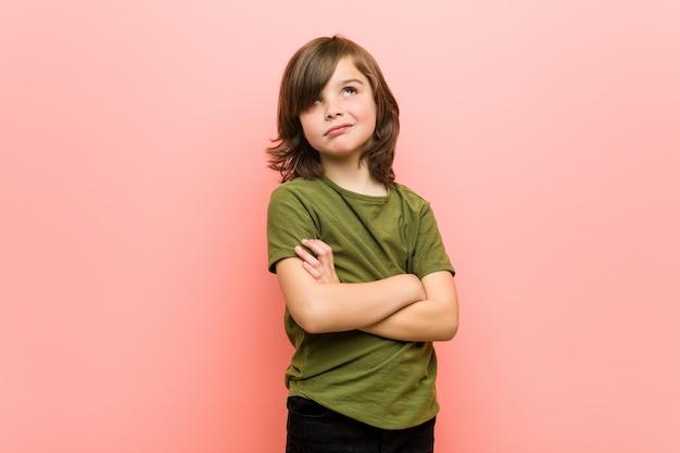 Petit garçon malheureux regardant à huis clos avec une expression sarcastique.