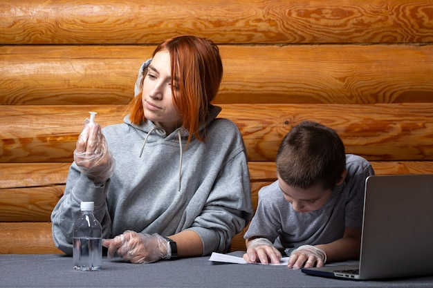Petit garçon avec maman lit les instructions pour les travaux de laboratoire