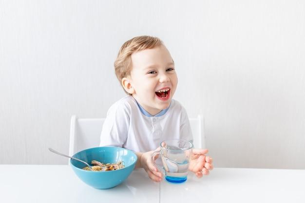 Le petit garçon mange avec une cuillère à la maison, le concept de nourriture et de nutrition pour les enfants