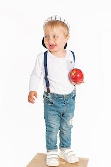 Petit garçon mange des pommes et souriant dans le studio isolé