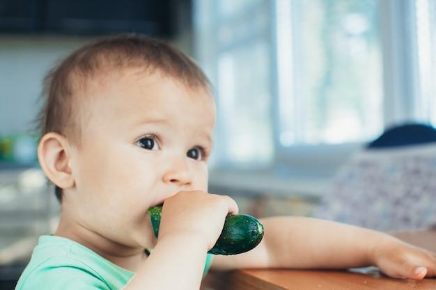 Petit garçon mangeant un concombre frais dans la cuisine à la lumière du jour