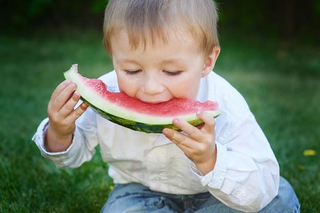 Petit garçon mangeant des pastèques dans le jardin d'été