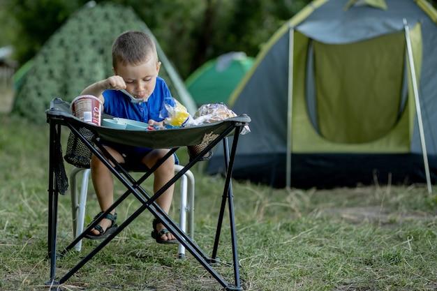 Petit garçon mangeant son petit-déjeuner en plein air au camping dans la nature au soleil avec une tente