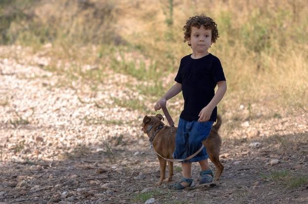 Petit garçon marchant et jouant avec son petit chien en forêt loin du danger de la ville