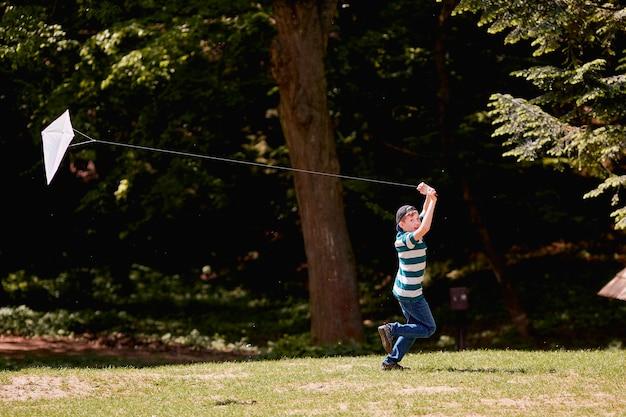 Le petit garçon marche et joue avec le cerf-volant