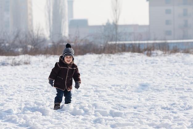 Le petit garçon marche sur le sol enneigé