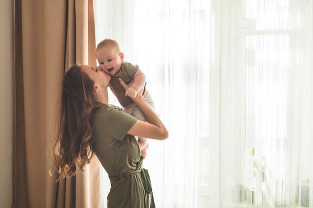 Petit garçon avec mère près de la fenêtre