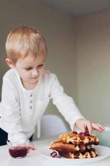 Petit garçon met des fruits sur une gaufre