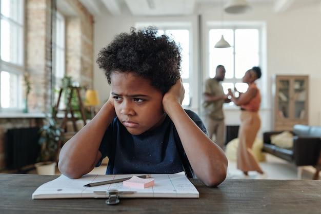 Petit garçon métis agacé se couvrant les oreilles avec les mains alors qu'il était assis près d'une table et essayant de faire ses devoirs contre ses parents ayant une rangée