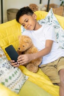 Petit garçon métis contemporain tenant un smartphone au-dessus de la table avec ses jouets tout en prenant une photo de la composition à la maternelle