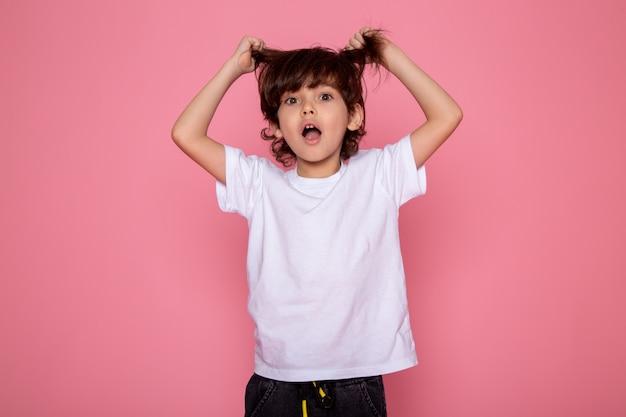 Petit garçon mignon adorable doux en t-shirt blanc et pantalon gris sur mur rose
