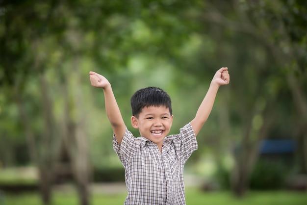Petit garçon mignon, appréciant élever des mains avec la nature sur le fond de nature floue.