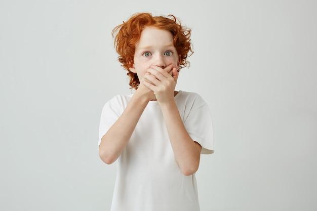 Petit garçon mignon au gingembre aux yeux verts dans la bouche de vêtements de t-shirt blanc avec les mains, ayant peur de regarder un film d'horreur avec des amis.