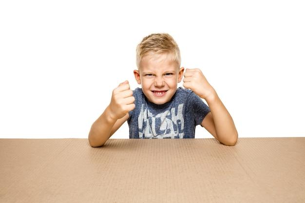 Petit garçon mignon et bouleversé ouvrant le plus gros colis postal