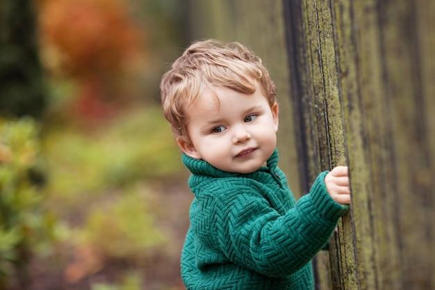 Petit garçon mignon dans le parc photo en gros plan du joli petit garçon dans le jardin d'automne activité en plein air