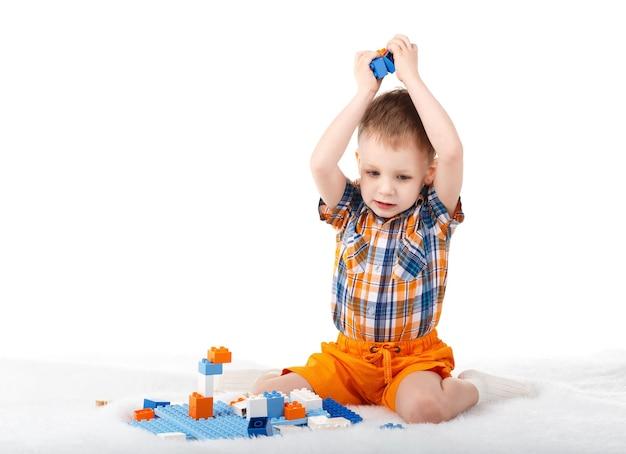 Petit garçon mignon jouant avec le concepteur sur le sol isolé sur blanc