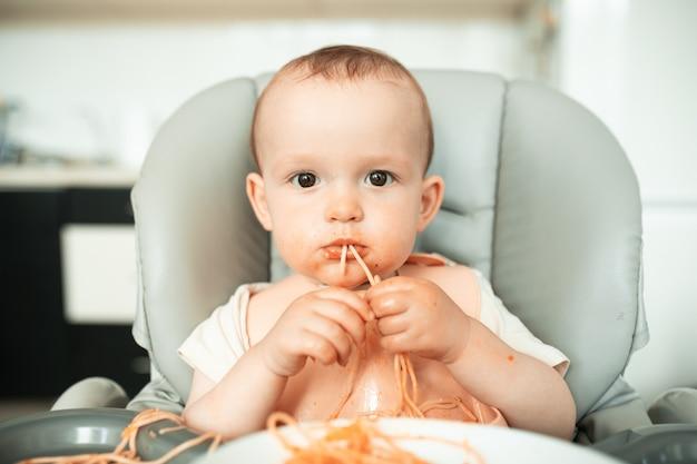 Un Petit Garçon Mignon Mange Des Spaghettis Avec Enthousiasme Et Se Salit Avec Des Scènes Familières Sous Rouge Dans La Cuisine... Photo Premium