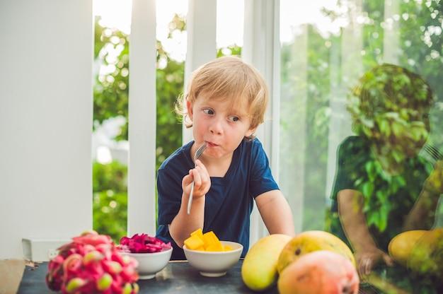 Petit garçon mignon mangeant de la mangue sur la terrasse.