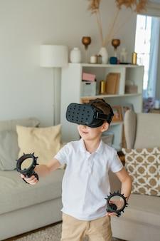 Petit garçon mignon regarde la réalité virtuelle avec des lunettes.