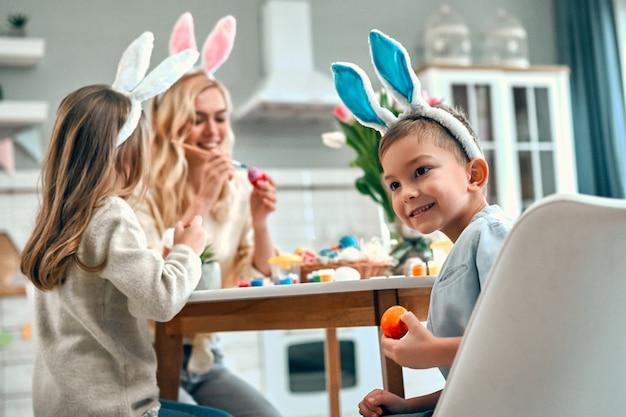 Un petit garçon mignon avec sa sœur et sa mère se préparent pour la célébration de pâques. une famille heureuse portant des oreilles de lapin passe du temps ensemble avant pâques tout en peignant des œufs.