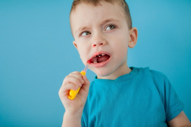 Petit garçon mignon se brosser les dents sur fond bleu.
