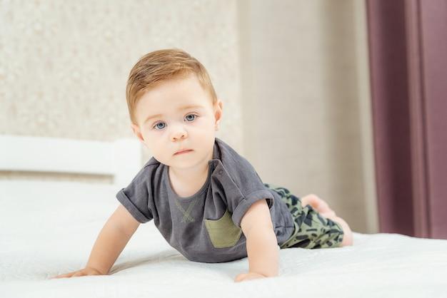 Le petit garçon mignon se trouve sur un lit et regarde la caméra. beau petit garçon aux grands yeux bleus.