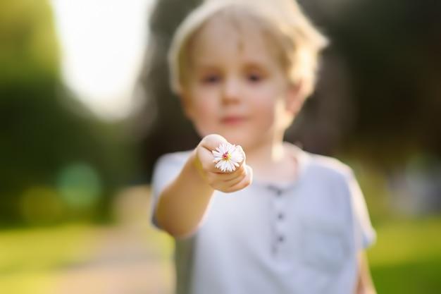 Petit garçon montre une fleur et pose une question