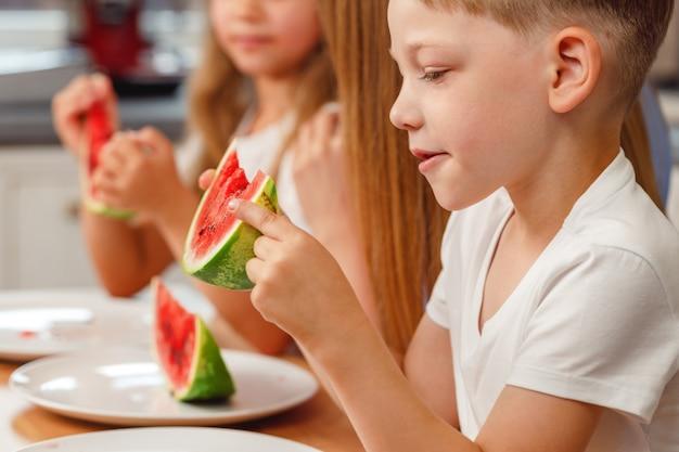 Petit garçon mordant une tranche de pastèque dans la cuisine