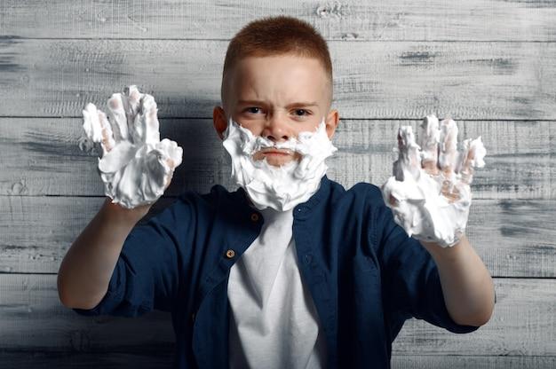 Petit garçon avec de la mousse à raser sur son visage et ses mains en studio.
