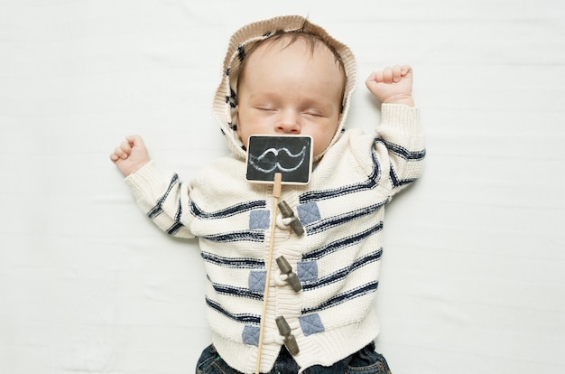 Petit garçon avec des moustaches décoratives allongé sur le lit