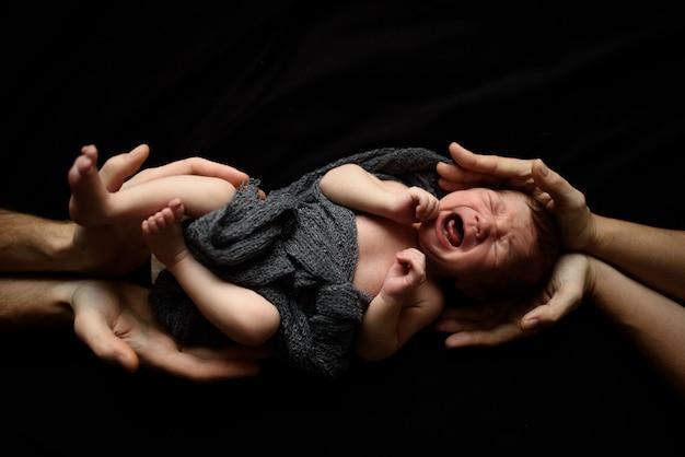 Petit garçon nouveau-né sur fond noir. le haut et le bas du garçon soutiennent les mains des parents.