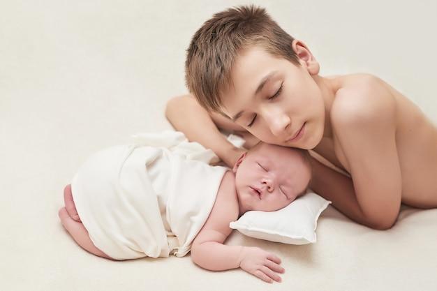 Petit garçon nouveau-né avec son frère aîné dormant sur fond blanc. concept de médecine et de santé, maternité et paternité heureuses. maternité et clinique. fête des pères et mères