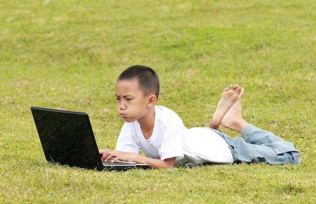 Petit garçon avec ordinateur portable sur l'herbe
