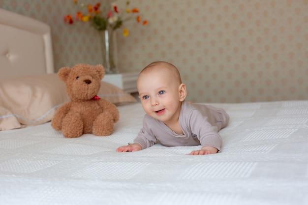 Un petit garçon avec un ours en peluche est allongé sur le lit dans la chambre sur le ventre