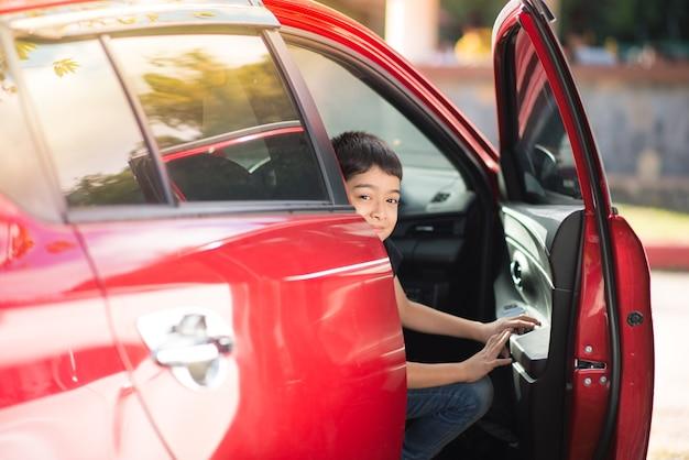 Petit garçon ouvrant la porte de la voiture