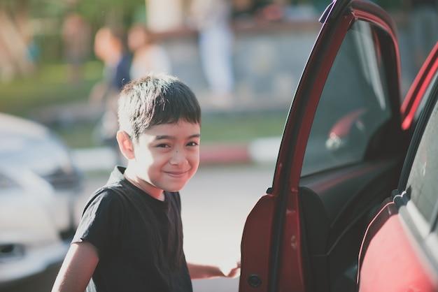 Petit garçon ouvre la porte de la voiture pour entrer à l'intérieur