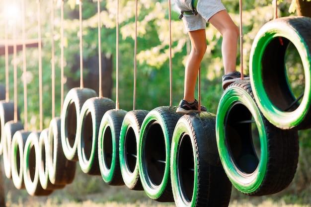 Un petit garçon passe l'obstacle dans le parc de corde