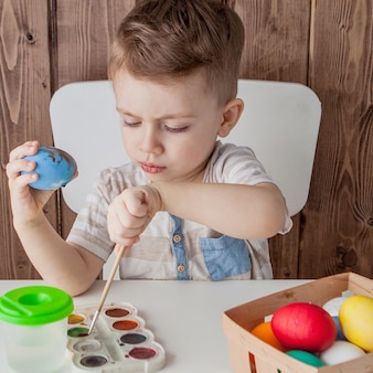 Petit garçon peignant des oeufs colorés pour pâques sur fond de bois