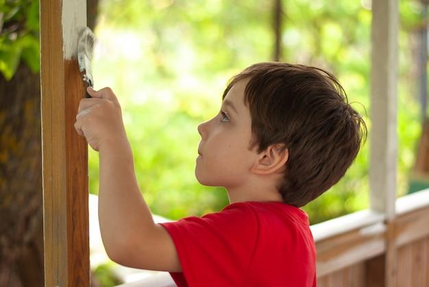 Petit garçon peinture bâtiment en bois avec pinceau