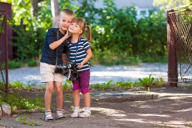Petit garçon et une petite fille avec deux caméras vintage debout ensemble