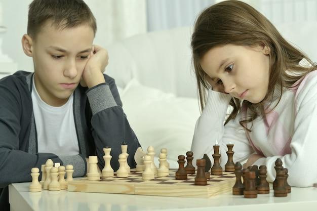 Petit garçon et petite fille jouant aux échecs à la maison. enfants jouant aux échecs