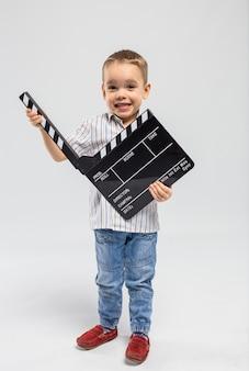 Petit garçon avec planche de battant au studio