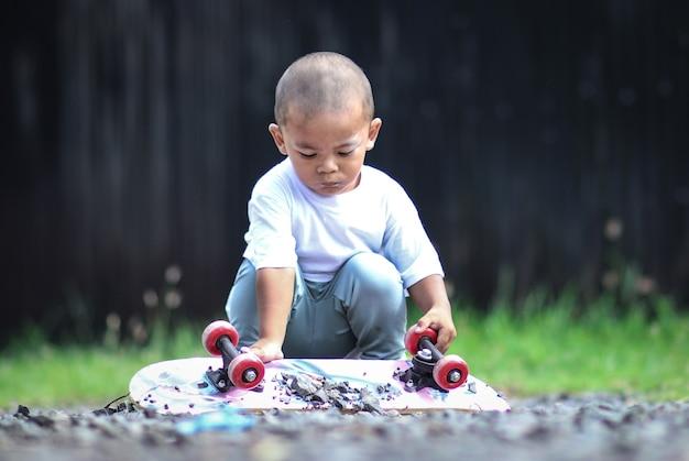 Petit garçon sur planche à roulettes.