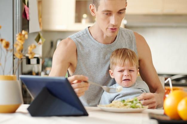 Petit garçon pleurant pendant le déjeuner pendant que son père essaie de le nourrir à table dans la cuisine