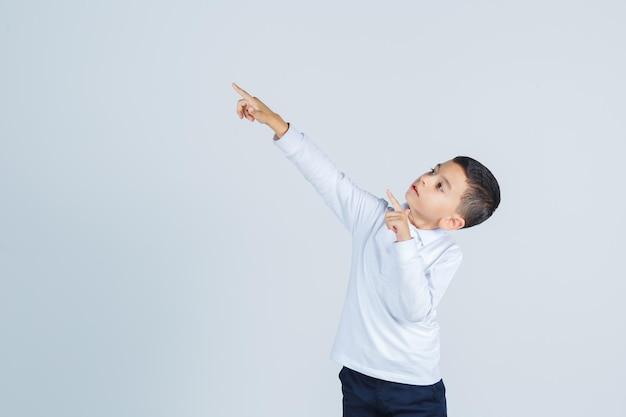 Petit garçon pointant vers le coin supérieur gauche en chemise blanche, pantalon et l'air confiant. vue de face.