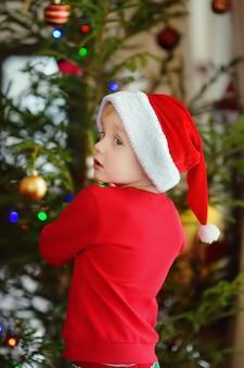 Petit garçon portant un bonnet de noel prêt pour célébrer noël. enfant mignon décorer le sapin de noël avec un jouet en verre
