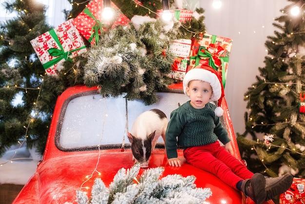 Un petit garçon portant un chapeau de père noël est assis sur le capot d'une voiture rouge avec un mini cochon, décoré d'arbres de noël avec des boîtes de cadeaux