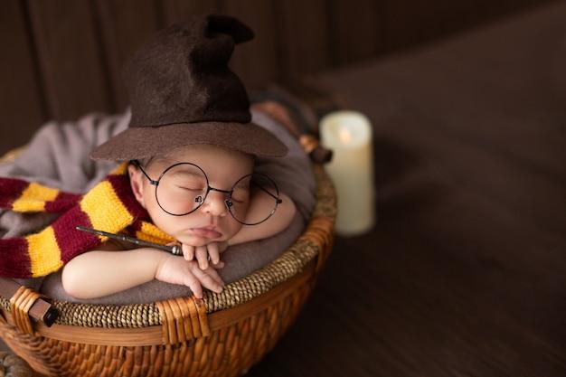 Petit garçon portant à l'intérieur d'un petit panier avec un costume de sorcier drôle